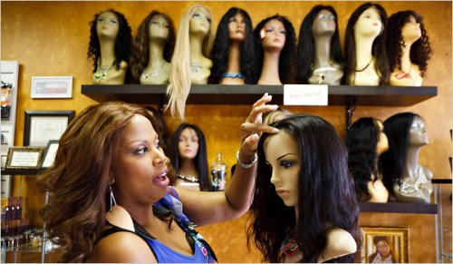 Salon owner Lisa Amosu fixing the hair on one of her lace wigs